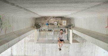 Minimalistyczna kawalerka ukryta pod betonowym mostem