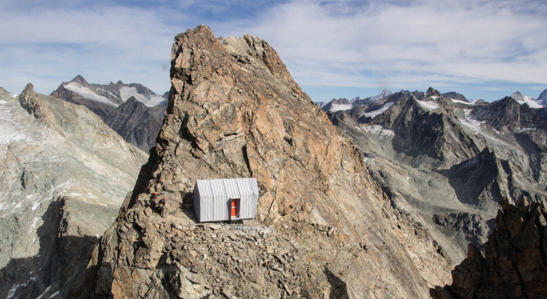 Chatka na szczycie góry, z której rozciąga się zachwycający widok na Alpy
