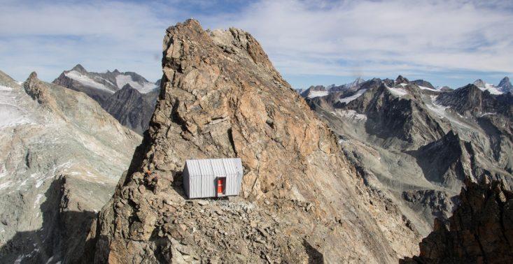 Chatka na szczycie g&oacute;ry, z kt&oacute;rej rozciąga się zachwycający widok na Alpy<